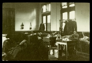The 'night nursery' in a building known as the Red Asylum, Bailleul, Belgium, 1915.  The building was used as a hospital by British forces from October 1914 until the evacuation of the town in April 1918.  Serious cases, e.g. trephines, chest and abdominal wounds, amputations etc., were kept in one ward, which was often called 'the nursery' by medical and nursing staff as the casualties were all so helpless.