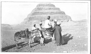 Photograph of a female tourist on a donkey being led towards a pyramid, Egypt 1925